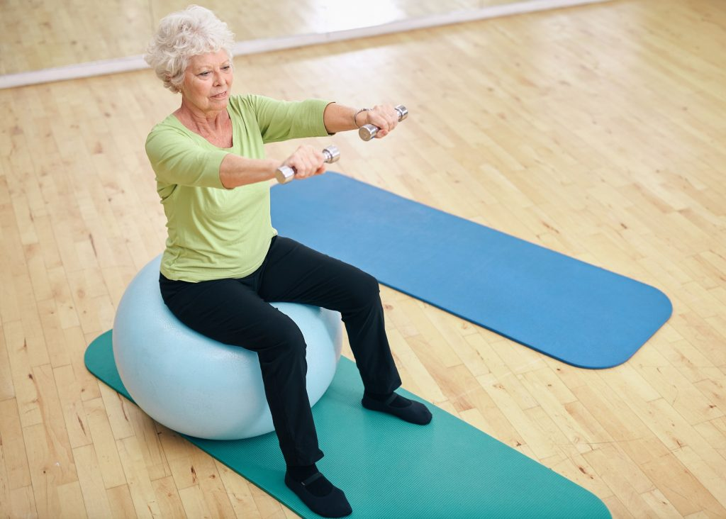 Senior female sitting on a fitness ball and lifting dumbbells. Old woman exercising with weights at gym.